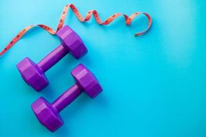 Fitness equipment dumbbells on color background