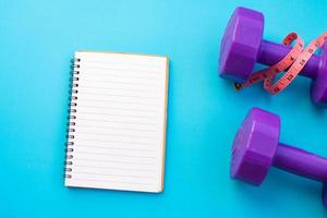 Dumbbells with notepad on blue background