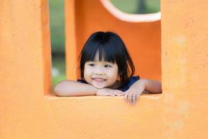 Young Asian girl in the window enjoys playground