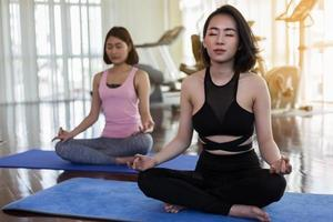 Two women doing yoga in the gym