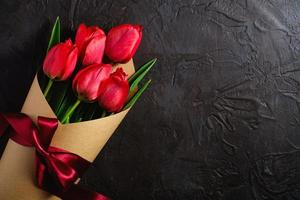 Bouquet of red tulips on textured black background