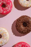 Chocolate, pink and vanilla donuts with sprinkles on pink background