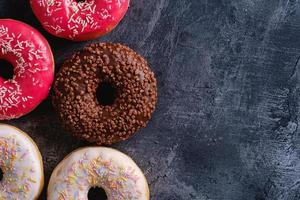 Colorful donuts with sprinkles on dark concrete textured background