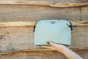 mujer con bolso azul sobre fondo de madera