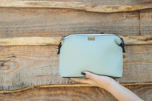 Woman holding blue handbag on wood background