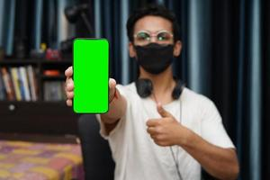 Young Indian boy holding a phone with green screen