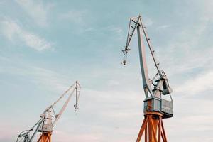 Construction cranes under blue sky