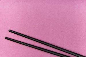Chopsticks on purple background photo
