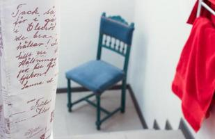 Words on curtain next to blue chair and red towel