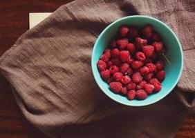 Raspberries in bowl with cloth photo