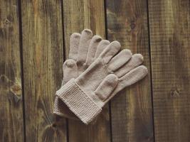 White knitted gloves on wooden surface photo
