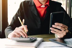 Empresaria mirando el teléfono inteligente y usando la calculadora