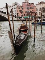 Gondola in water with Rialto Bridge and buildings