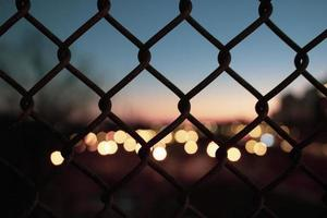 Silhouette  of fence and city lights, out of focus