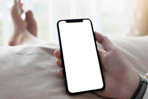 Close-up of person holding phone in bed photo