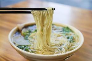 Close-up of chop sticks and bowl of ramen photo