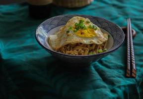 Bowl of noodles with fried egg photo