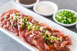 carne de cerdo fresca en rodajas con coberturas foto