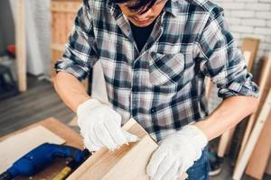 Craftsman is glueing wood together in work shop