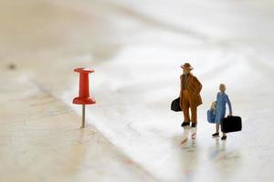 Small wooden human figurines stand on a map