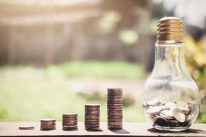 pilhas de moedas com lâmpada com moedas nele foto
