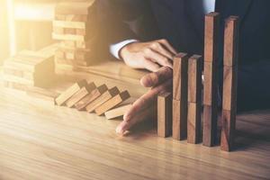empresario evitando la caída de bloques de madera