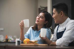 Couple in kitchen sit over coffee