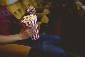 Man reaches for popcorn  in a cinema