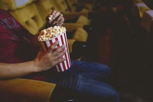 man reikt naar popcorn in een bioscoop