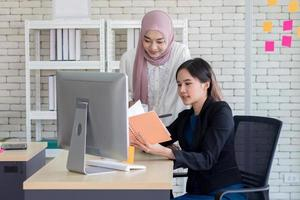Two women coworkers collaborating in office