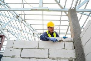 Construction worker building brick wall