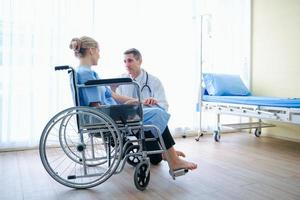 A doctor is talking with patient in wheelchair