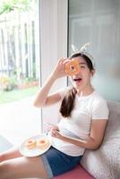 Asian woman holding donut and tablet