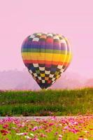 Colorful hot air balloon landing in field