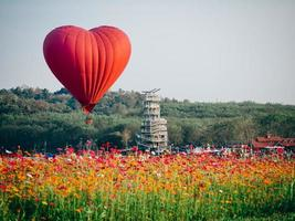 Red heart-shaped air balloon over field of flowers
