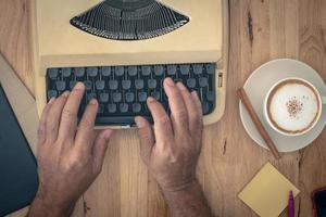manos usando máquina de escribir vintage foto