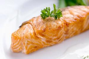Salmon steak with white sauce on a white plate