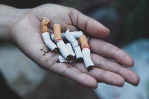 manos rompiendo cigarrillos