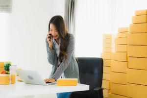 Businesswoman making a call and working on computer with packages behind her