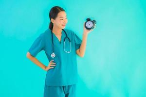 Portrait of woman doctor holding alarm clock