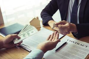 agente inmobiliario que da la llave de la casa al cliente