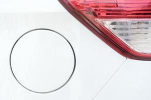 Close up of tail light and gas cap on white car