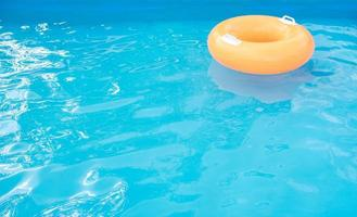 Orange inflatable tube in swimming pool.
