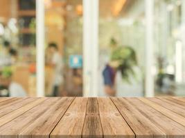 Wooden tabletop in front of blurred coffeeshop background