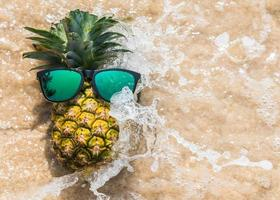 Pineapple and sunglasses splashed with waves