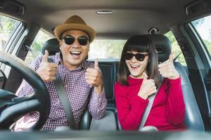 Man and woman give thumbs up in car
