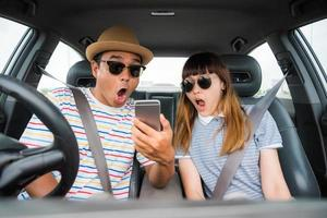 Couple looking shocked at phone in car