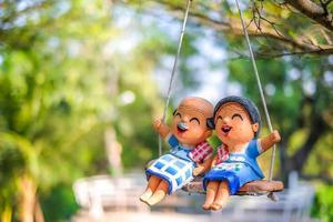 Toy couple swinging in the sun