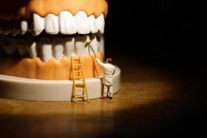 hombre miniatura pintando dientes blanco