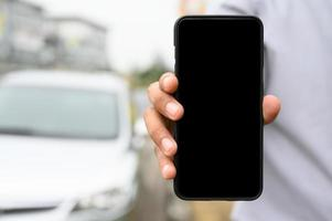 Close-up of person holding phone with cars in background